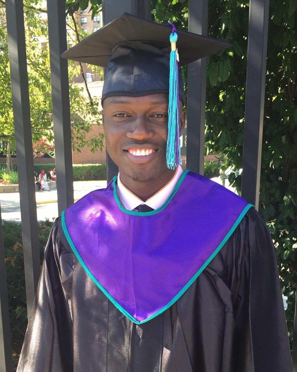 cheick in cap and gown on graduation day